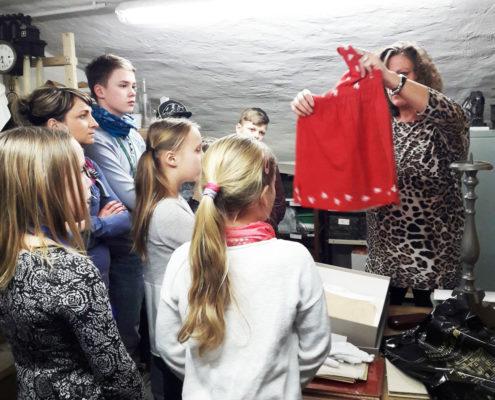 HistoryKids im Depot des Kreismuseums: Leiterin Manuela Vehme zeigt den Kindern das aus Fahnenstoff genähte Kleid und erzählt die Geschichte dazu. (Foto: Ulrike Unger)