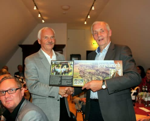 Der Geschichtsvereinsvorsitzende Dr. Norbert Rohde überreicht dem Vorsitzenden des befreundeten Heimatvereins, Dr. Alois Thomes, ein Gastgeschenk.