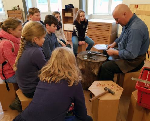 Schmied und Metallkünstler Olaf Hannemann erklärt den Kindern die Technik der Metallbearbeitung (Foto: Babett Wiechmann)
